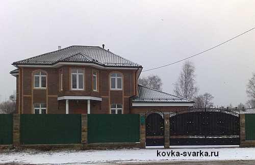 кирпичный дом и кованые ворота