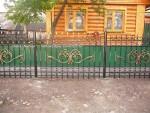 Металлический забор, украшенный элементами художественной ковки